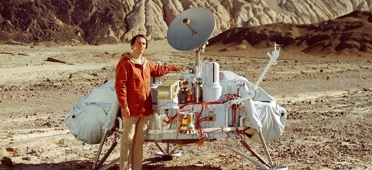 Photograph of Carl Sagan with a model of the Viking lander.