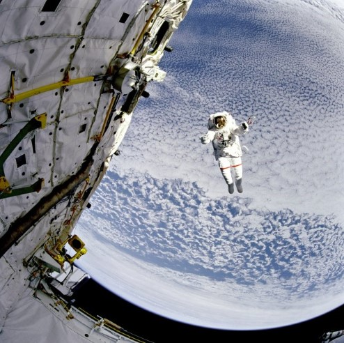 Photograph of astronaut Mark C. Lee above the Earth.