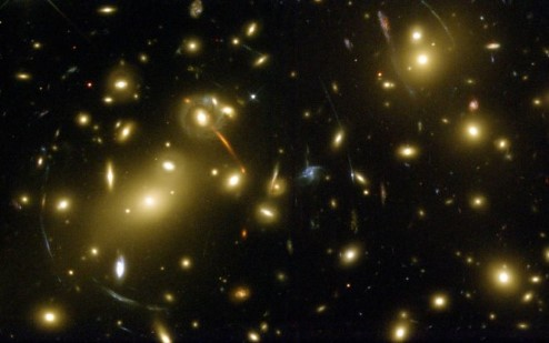 Photograph of galaxies, some of their shapes are distorted by gravitational lensing.